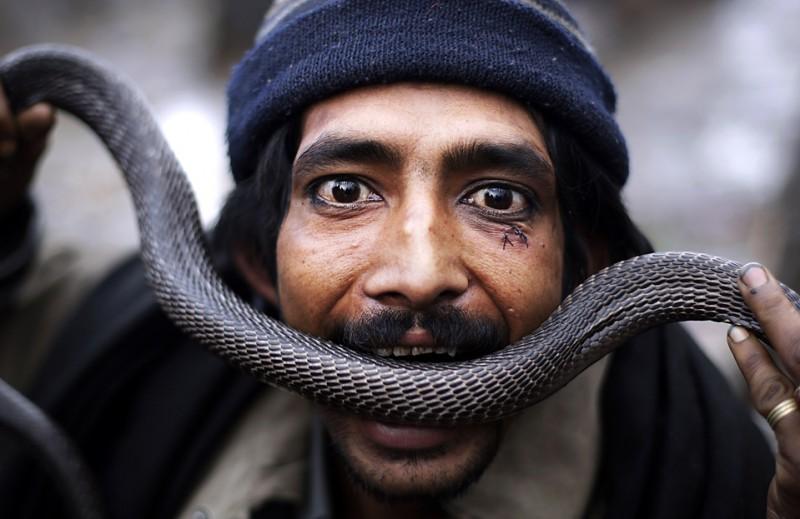 2. Уличный артист выступает со змеей на дороге недалеко от Исламабада. (Muhammed Muheisen/Associated Press)