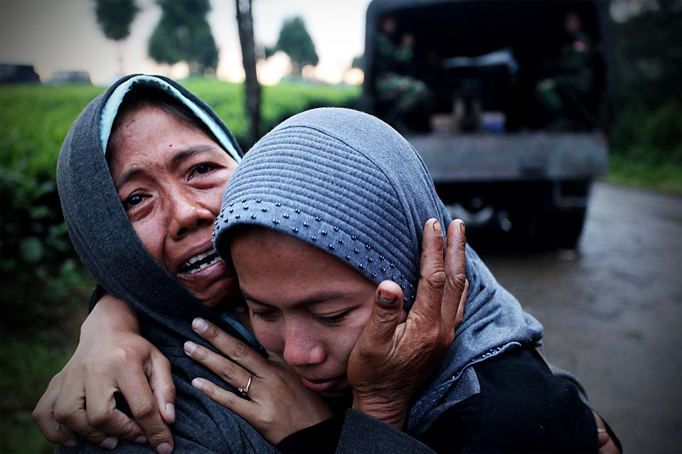 3. Жители деревни Девата скорбят по погибшим в результате оползня в Индонезии. С тех пор, как сильные ливни вызвали оползни на чайной плантации, из-под грязи и обломков были вытащены 17 тел. (Ulet Ifansasti/Getty Images)