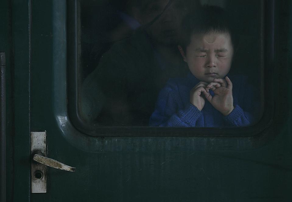 5. Ребенок закрыл глаза в поезде, покидающем станцию Вучанг в Ухане, провинция Хубэй. (Wang He/China Foto Press/ZUMA Press)