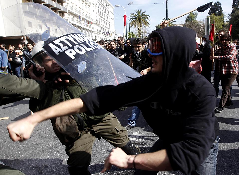 8. Демонстрант дерется с полицейским на антиправительственном митинге в Афинах. Десятки тысяч человек вышли на улицу греческой столицы, протестуя против жестких экономических мер. (Yiorgos Karahalis/Reuters)