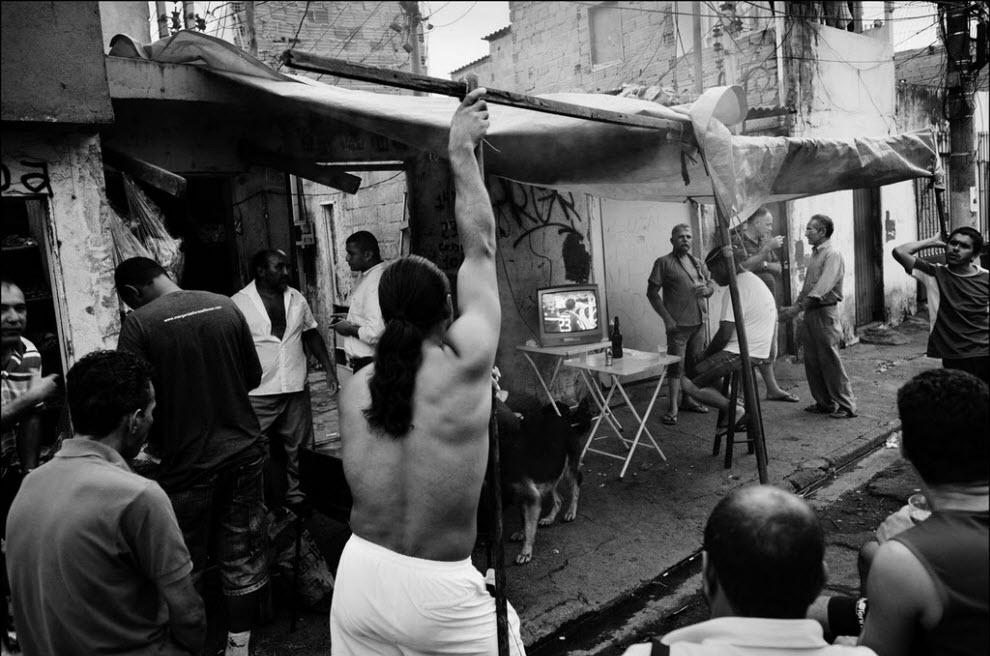 02) Мужчины смотрят по телевизору футбол в баре.