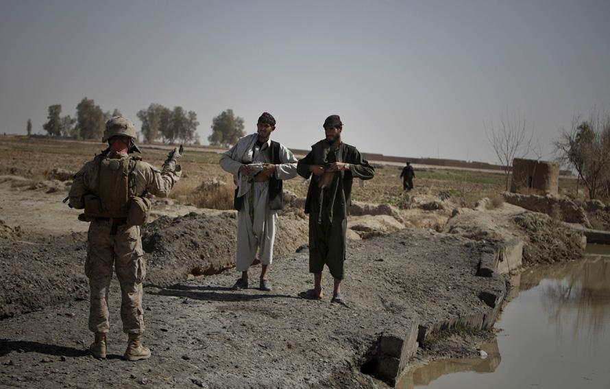 2. Морпех сил НАТО приказывает афганцам поднять одежду, чтобы убедиться, что у них нет оружия, в Маржахе 17 февраля. (AP Photo/Altaf Qadri)