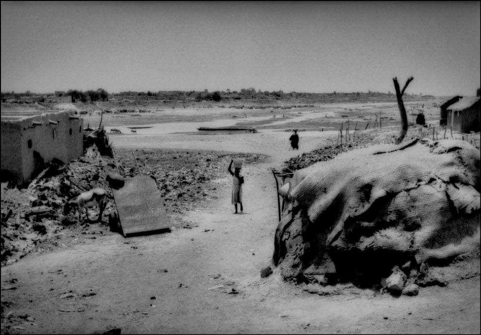02) Женщина несет воду из почти высохшей реки Мопти, Мали.
