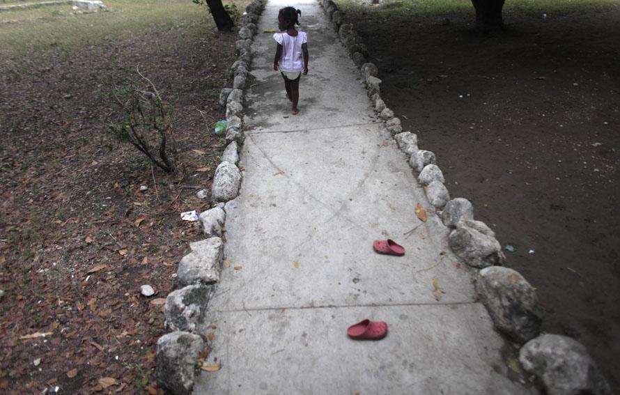 """2. Девочка разулась у входа в приют, управляемый """"SOS Children's Villages International» - австрийской некоммерческой организацией. Этот приют в Порт-о-Пренс предоставляет крышу сиротам и помогающий с поисками пропавших родственников . Многие дети лишились родителей в результате крупного землетрясения 12 января. (AP Photo/Dario Lopez-Mills)"""
