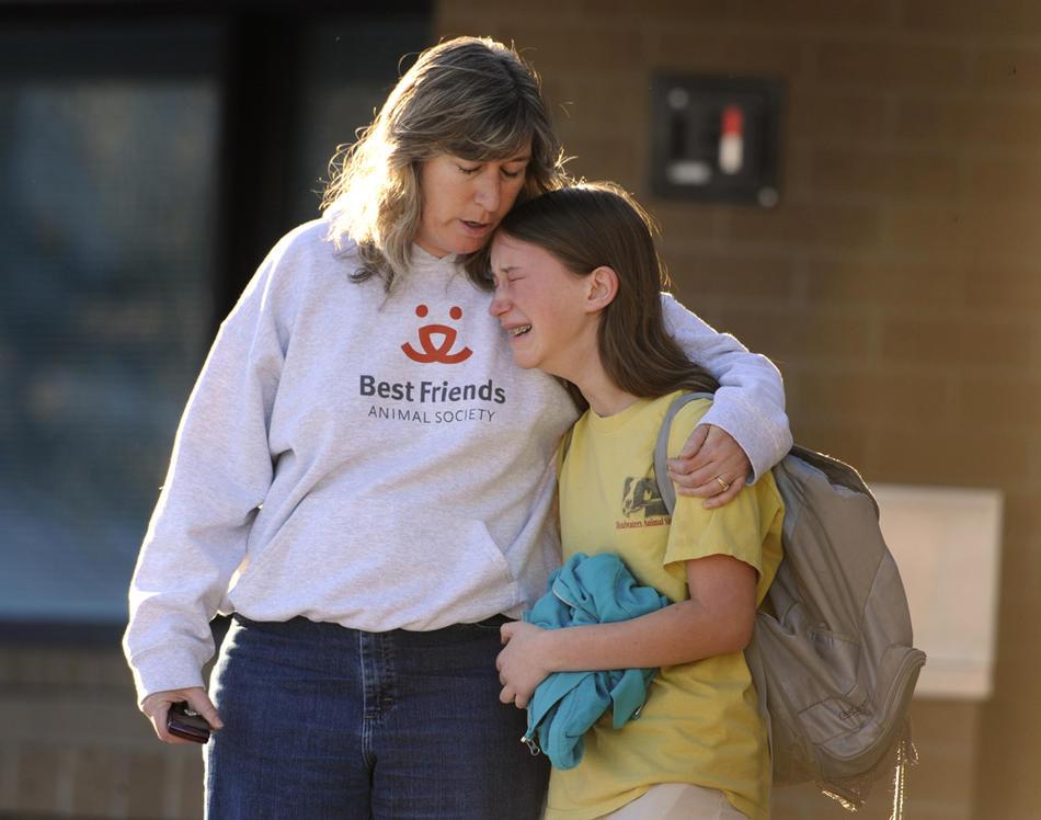2. Дебби Сентер успокаивает свою дочь 13-летнюю Диану, которая была в школе, когда началась стрельба. Диана была в это время в библиотеке. Учеников школы спешно эвакуировали в соседнюю начальную школу «Stony Creek», куда приехали их родители. (Kathryn Scott Osler / The Denver Post)