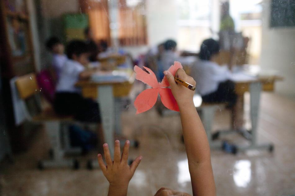3. Девочка рисует на стекле в классе, где занимаются дети, больные СПИДом. (Justin Mott/The New York Times)