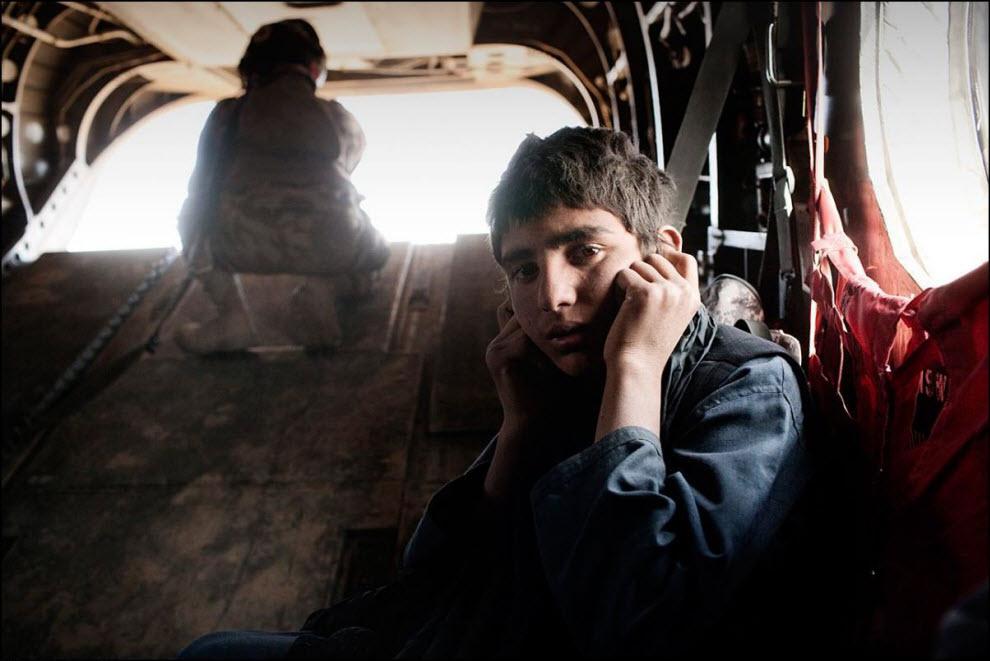03) Афганский ребенок закрывает уши от шума вертолета.