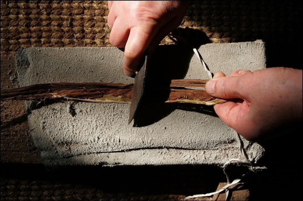 4) Рабочий обдирает кору с дерева, чтобы отправить ее потом на смешивание. (Getty Images/Chung Sung Jun)