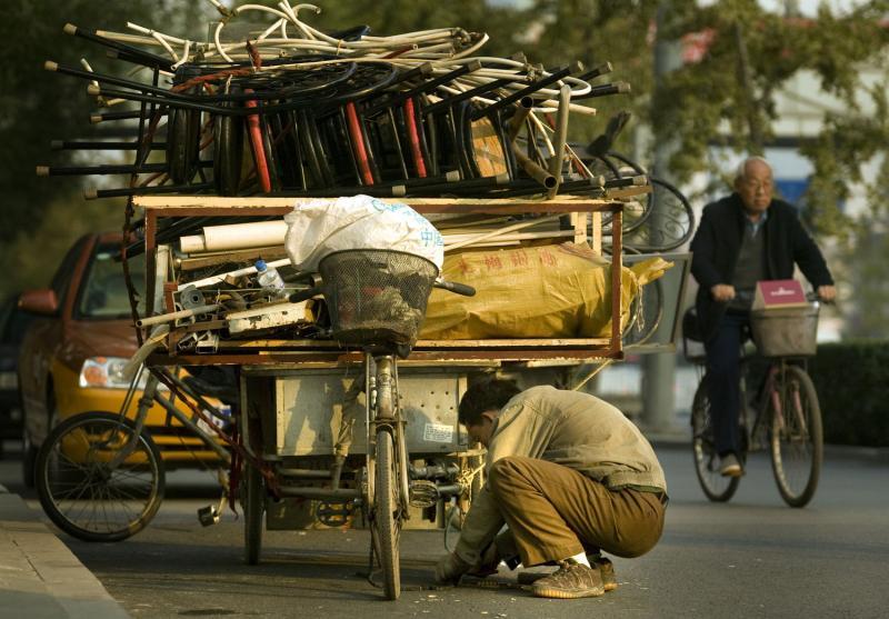 4. Китайский мигрант чинит сломанную цепь на своем перегруженном мусором велосипеде в Пекине 13 ноября 2008 года. (UPI Photo/Stephen Shaver)