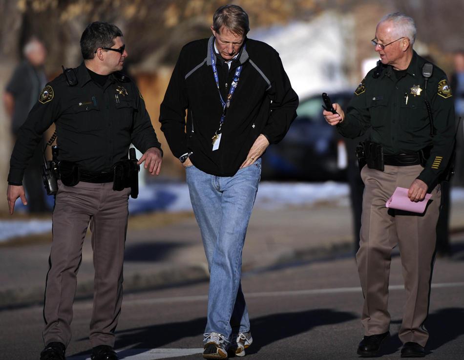 4. Офицеры полиции округа Джефферсон сопровождают доктора Дэвида Бенке в автомобиль для дачи более подробных показаний в участке. (AP Photo/The Denver Post, Joe Amon)
