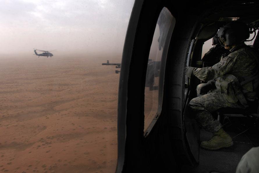 4. Воздушный стрелок, стреляющий через дверь вертолета, специалист Фредди Зазуета из компании Чарли 2-82 оперативной группы Талон летит на вертолете «Черный ястреб», который сопровождает вертолет эвакуации над долиной Гильменд. (AP Photo/Brennan Linsley)