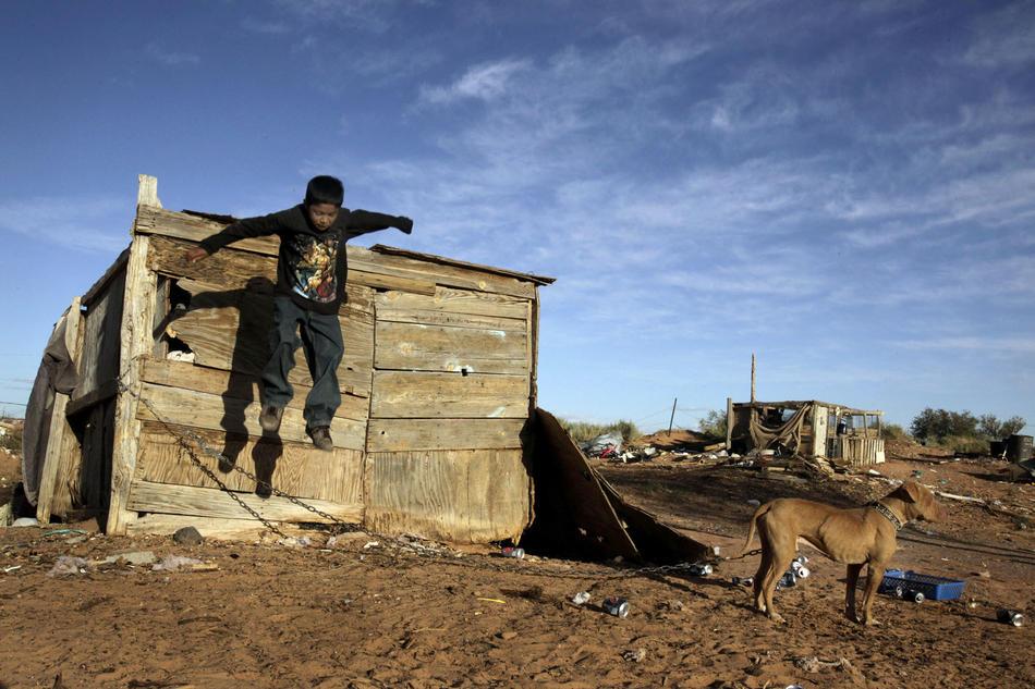 5. 8-летний Хулио Алмейда спрыгивает с крыши одного из сараев на заднем дворе. Он живет с мамой и пятью братьями и сестрами в трейлере недалеко от города Туба, штат Аризона. В трейлере есть электричество. (Los Angeles Times photo by Barbara Davidson)