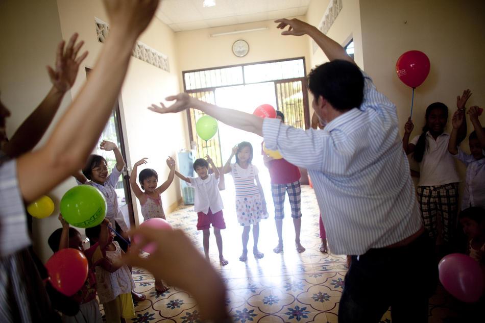5. Местные добровольцы приносят игрушки, игры и угощения сиротам в приюте Маи Хоа. (Justin Mott/The New York Times)