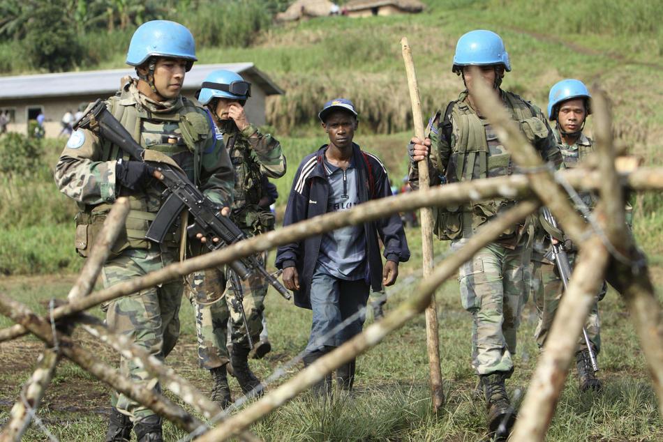 5. На этом фото, сделанном 5 октября 2009 года, уругвайские миротворцы сопровождают руандийского мятежника Элиаса Санвура (в центре) в Кимуа. (AP Photo/Rebecca Blackwell)
