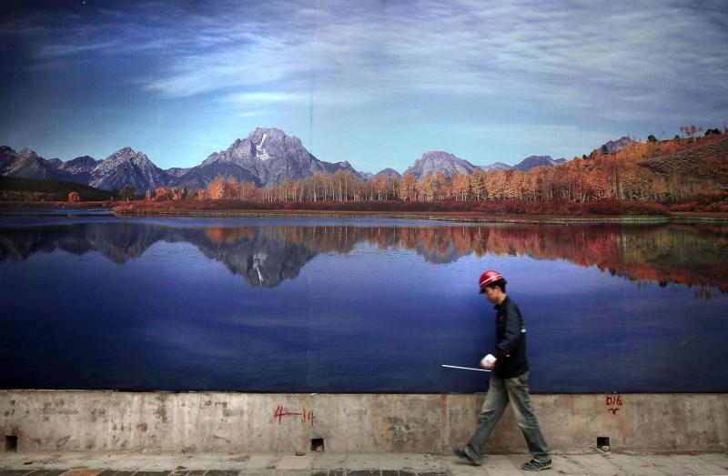 5. Китайский строитель проходит мимо огромного плаката одного из крупнейших озер Китая в Пекине. Многие строители приезжают в Пекин из сельских местностей в надежде найти хорошую работу с более высокой оплатой. (UPI Photo/Stephen Shaver)