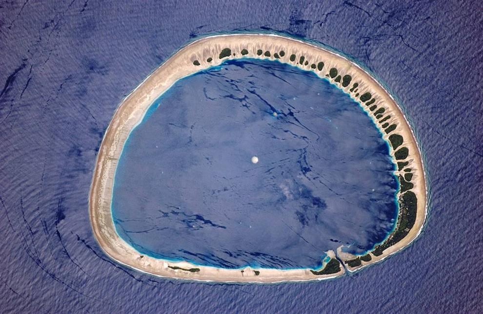 5. Астронавты проходят по орбите над западной частью Тихого океана, они долго не видят сушу. Затем появляются атоллы и коралловые рифы, тогда-то астронавты и тянутся к своим камерам. «Они видят эти жемчужины в океане и хотят запечатлеть их в детальном виде», - говорит Эванс. Атолл Нукуоро на островах Каролин на северо-востоке Папуа Новой Гвинеи были запечатлены 31 мая 2006 года. 42 «островка» зелени на острове обдуваются восточными ветрами. На острове небольшими поселениями живет около 900 человек. Изображения, сделанные с Международной космической станции используются специалистами по охране окружающей среды, чтобы отслеживать состояние здоровья подобных мест. (Image Science & Analysis Laboratory, NASA Johnson Space Center)