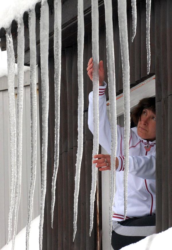 5. Женщина осматривает огромные сосульки, свисающие с крыши у окна ее дома на окраине Будапешта. (AP Photo/MTI, Gyula Czimbal)
