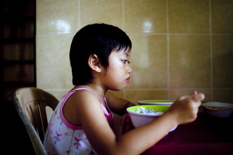 6. Девочка обедает в приюте Маи Хоа. Этим сиротам с ВИЧ нельзя ходить в обычную школу, так как родители «нормальных» детей боятся, что их дети могут заразиться. (Justin Mott/The New York Times)