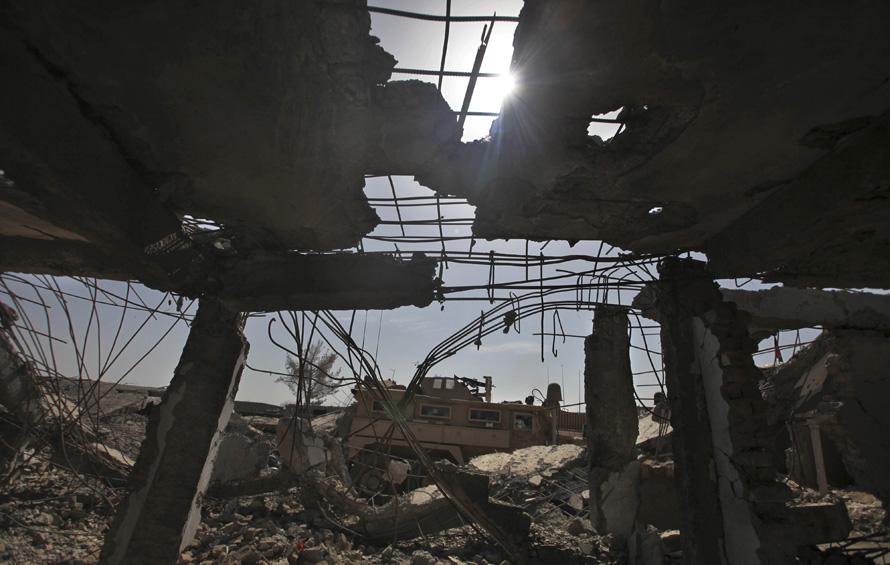 6. Бронетранспортер проезжает мимо обломков магазина в Маржахе. (AP Photo/Altaf Qadri)