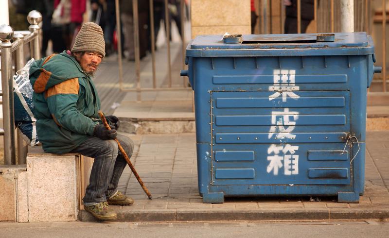 6. Китайский бездомный ждет рядом с мусорным баком, чтобы собрать бутылки или другой мусор. 15,3% из всех 130 миллионов мигрантов, переехавших с ферм и деревень в города снова вернулись домой, так и не найдя работу. (UPI Photo/Stephen Shaver)