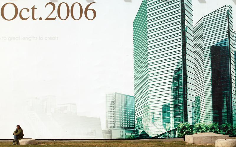6. Рабочий-мигрант отдыхает у огромного плаката, рекламирующего новый крупный коммерческий и жилой комплекс с отелем «Ritz Carlton» в Пекине. И хотя многое в жизни Пекина остается тем же вот уже несколько десятилетий, столица Китая потеряла почти половину своих районов сельского типа, так как правительство и частные компании активно занялись перестройкой города. (UPI Photo/Stephen Shaver)