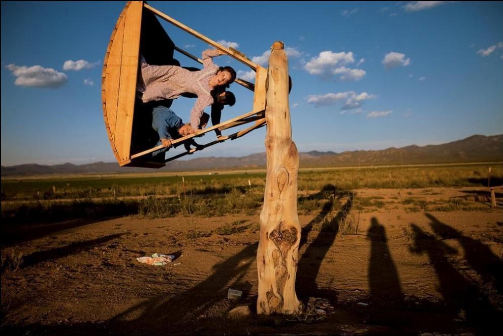 6) Девочка подросток катается на качелях, после того как отработала на ферме. (С) Stephanie Sinclair