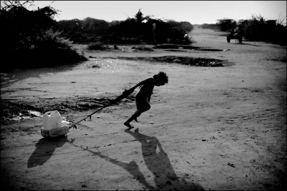 06) Девочка несет воду в лагере Дадааб.