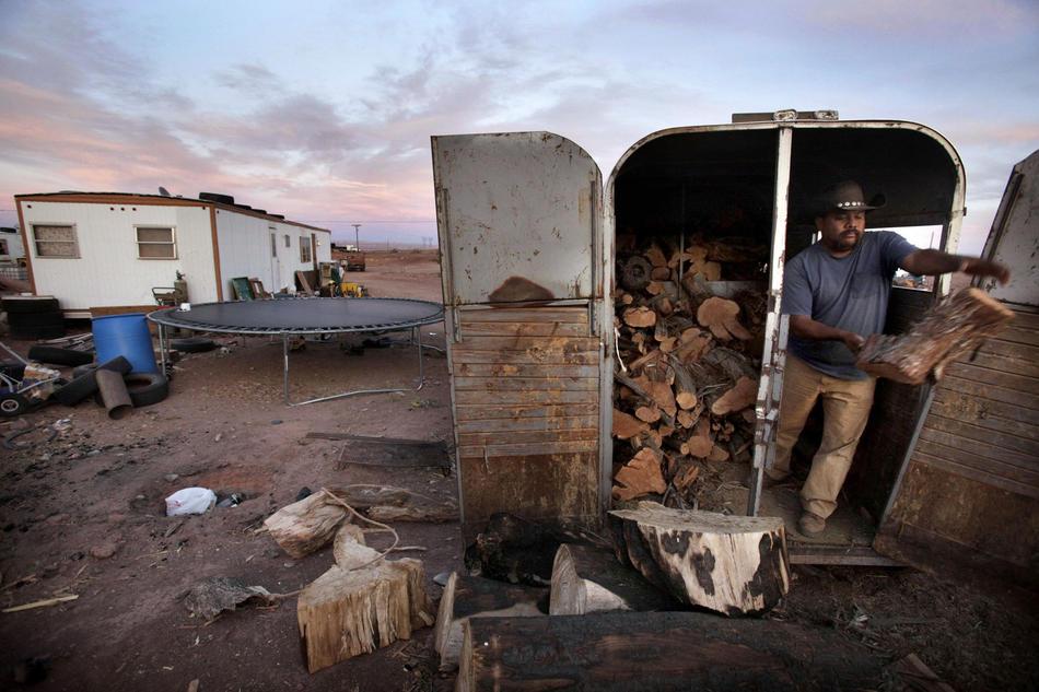 7. Ларри Горди выгружает бревна из своего трейлера в Кэмероне, штат Аризона. Его семья была вынуждены покинуть свое ранчо за городом после «заморозки Беннетта» в 1966 году, которая запрещала жителям даже проводить электричество. (Los Angeles Times photo by Barbara Davidson)
