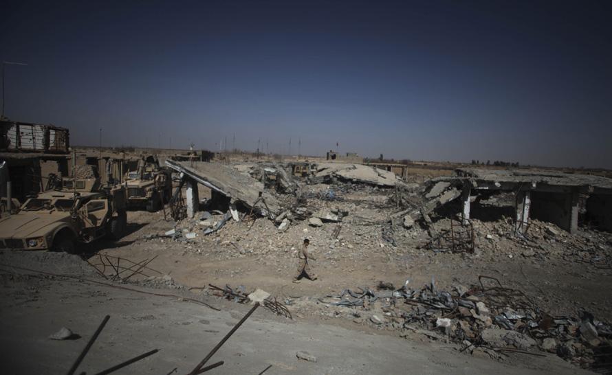 7. Невооруженный морпех проходит мимо разрушенного рынка в Маржахе. (AP Photo/Altaf Qadri)