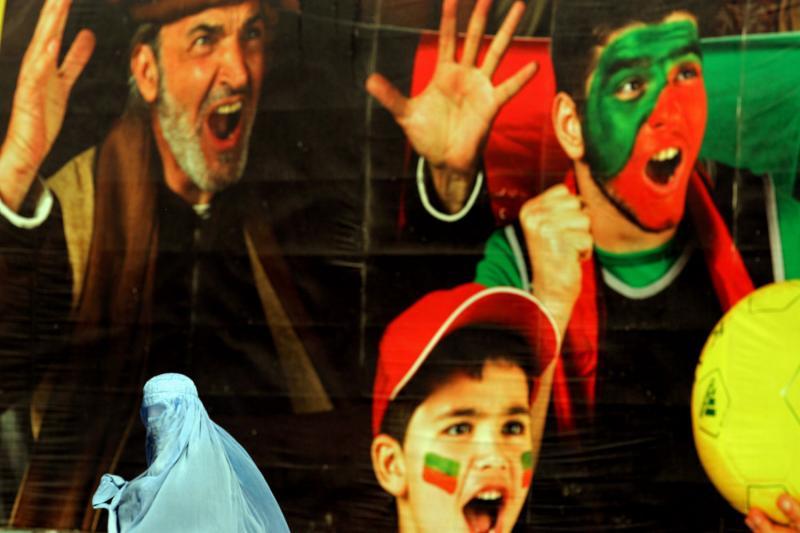 7. Женщина в парандже проходит мимо рекламного щита в Кабуле. (UPI/Mohammad Kheirkhah)