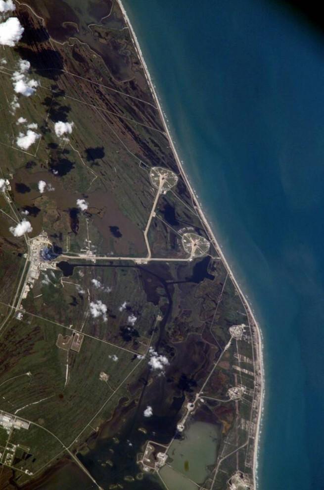 7. Этот снимок был сделан 6 апреля 2005 года, когда станция проходила над космическим центром Кеннеди во Флориде, когда шаттл «Discovery» готовили к запуску на платформе 39-B. Шаттл воссоединился с реактивным ускорителем на твердом топливе примерно на полпути 13-часового путешествия из здания сборки (слева на фотографии) до платформы (вверху в центре). Шаттл успешно взлетел 26 июля 2005 года и доставил весь необходимый груз на станцию. (Image Science & Analysis Laboratory, NASA Johnson Space Center)