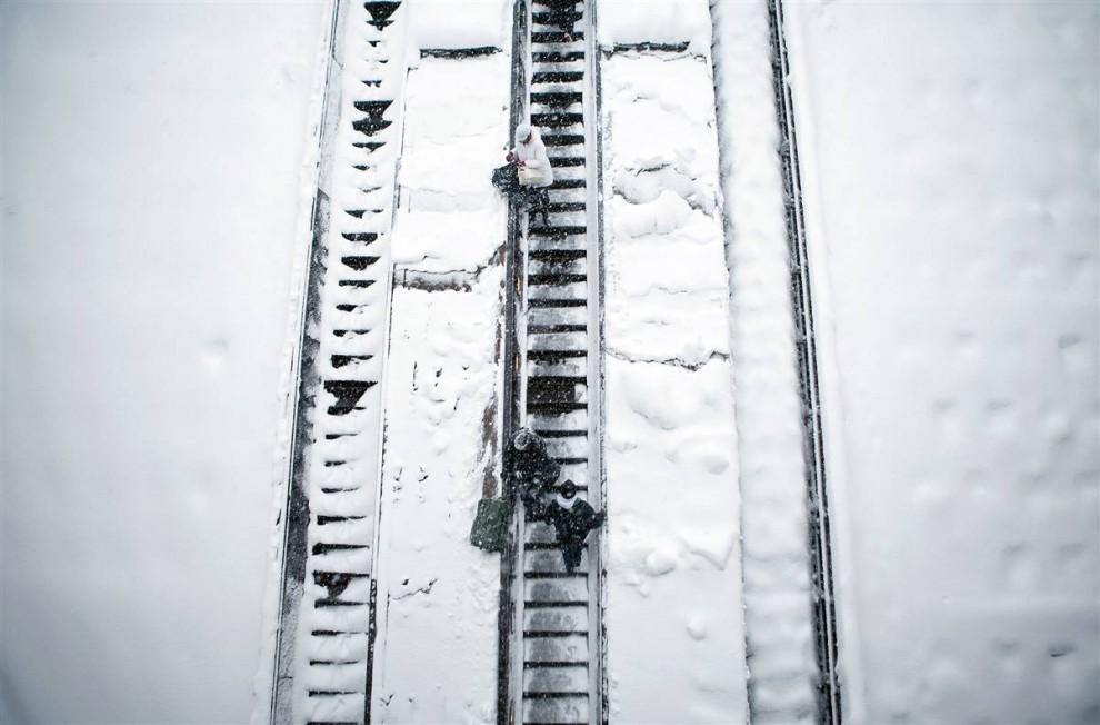 8. Люди спускаются с эскалатора в метро Дюпонт Серкл во время сильного снегопада в Вашингтоне 6 февраля. В городе выпало рекордное количество снега, и метеорологи обещают новые осадки. (Brendan Smialowski / Getty Images)