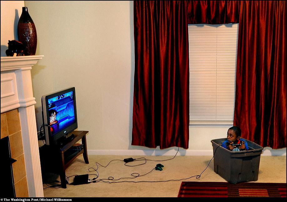 8) Милик Вайт играет в видеоигру сидя в пластиковой коробке для игрушек.