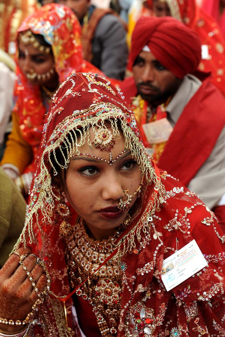 """Портрет индийской невесты сделанный во время массовой свадебной церемонии в Амритсаре. В свадьбе приняли участие 35 пар, которые проживают на территории у границы Индии и Пакистана и не могут себе позволить обычную свадьбу. Обычно сезон свадеб в Индии длится с середины октября по январь, а потом снова возобновляется с апреля по июль. При организации свадеб тут руководствуются принципом """"чем больше, тем лучше"""", поэтому идийская свадьба - это дорогое мероприятие, наиболее шикарные из которых обходились до 44 тысяч долларов. (NARINDER NANU/AFP/Getty Images)"""