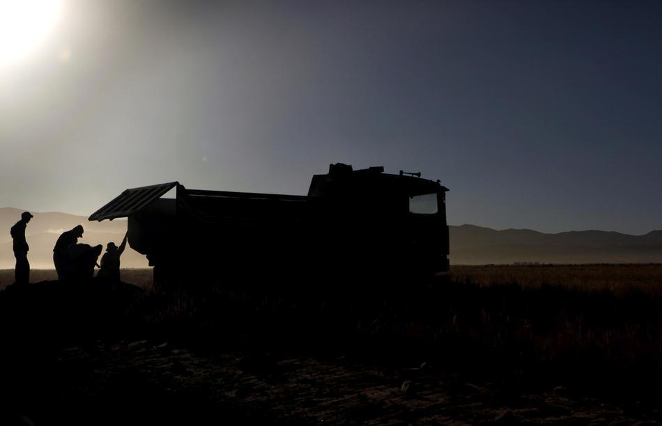 9. Рабочие грузят песок в грузовик, чтобы отвезти на стройплощадку недалеко от деревни. (AP Photo/Dado Galdieri)