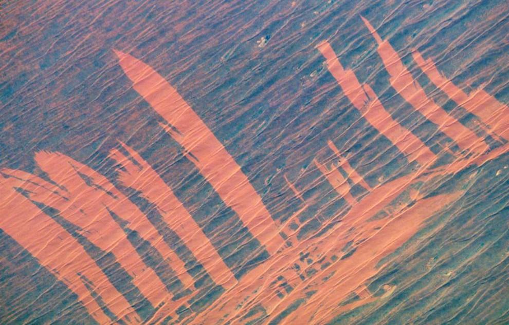 10. Разбушевавшийся в пустыне Симпсона в Авсралии огонь оставил на ней красные шрамы. Оранжевые полосы на этом снимке 23 ноября 2002 года появились, когда огонь прошелся по пустынным скрабам, обнажая песчаные дюны под ними. По узору можно предположить, что огонь двигался слева снизу по волнистым дюнам по направлению ветра. Затем ветер изменил направление где-то на 90 градусов, и огонь пошел поперек уже существующей полосы. Эти шрамы исчезнут с появлением новой растительности. (Image Science & Analysis Laboratory, NASA Johnson Space Center)