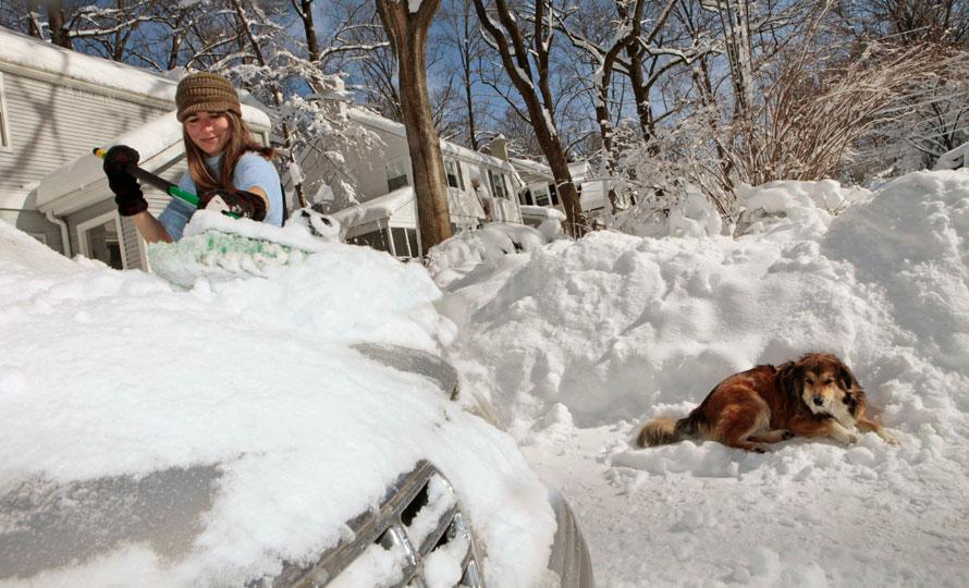 10. Мэри Кнапп Сайбель раскапывает свой автомобиль рядом со своей собакой по кличке Волк в Бетесде, штат Мэриленд. Города в среднеатлантической части США оказались в воскресенье под покрывалом снега, а спасательные команды пытались восстановить электричество в сотнях тысяч домов. (AP Photo/Charles Dharapak)