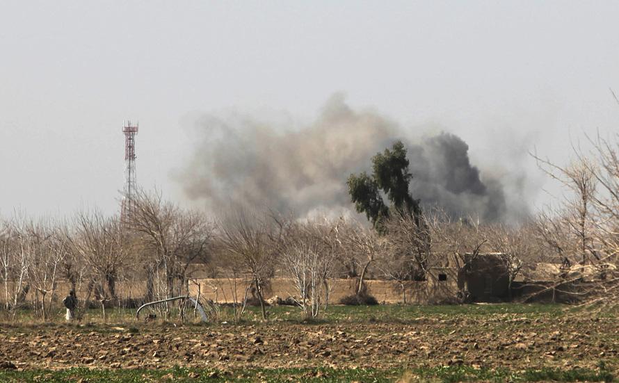 10. Афганец (слева) смотрит на поднимающийся в небо дым в Маржахе. (AP Photo/Altaf Qadri)