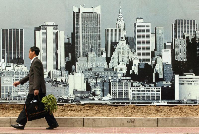10. Китайский бизнесмен с овощами (!) проходит мимо большого плаката, рекламирующего новый комплекс в стиле Нью-Йорка, в Пекине. В новых зданиях Китая 123 миллиона кв.м. незанятого пространства. В Пекине, Шанхае и других крупных городах Китая миллионы жителей просто выселяют, чтобы дать место роскошным домам и новым коммерческим проектам. (UPI Photo/Stephen Shaver)