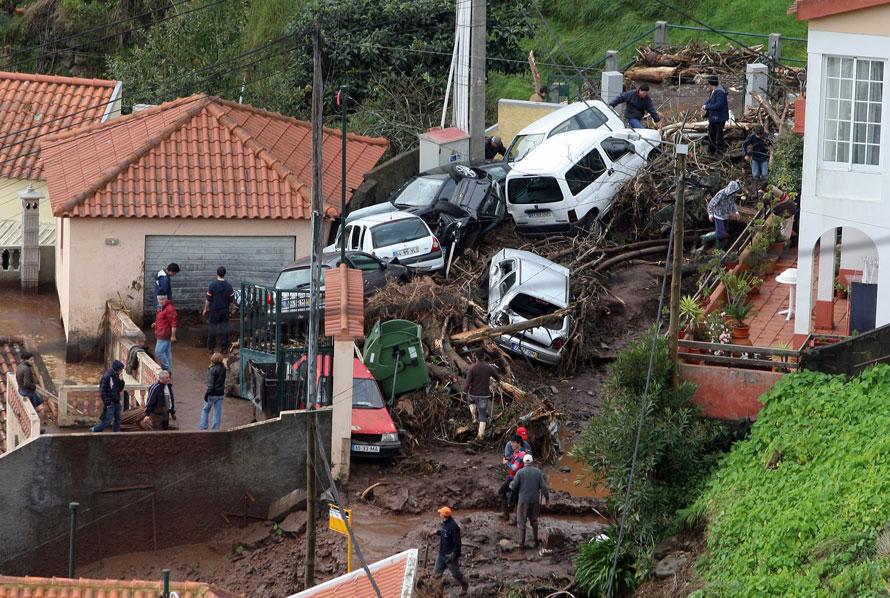 10. Автомобили кучей лежат у домов в столице острова Мадейра Фуншала. Автомобили принесло вниз по склону оползнем, вызванным сильными ливнями по всей Португалии. Местные власти оценивают жертвы, по меньшей мере, в 40 человек. (AP Photo/Octavio Passos)