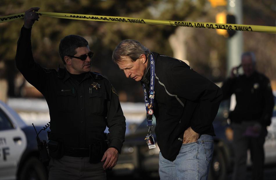 10. Доктор Дэвид Бенке (справа) уходит с места преступления в школе «Dear Creek». (Joe Amon / The Denver Post)