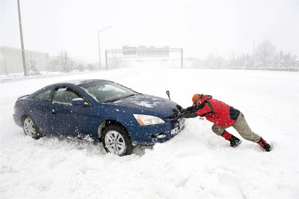11. Мэтт Кэролл помогает Джейку Хиатту из Александрии выехать из снежного заноса в центре шоссе Interstate I-395 в Спрингфилде, штат Вирджиния. (Cliff Owen / AP)