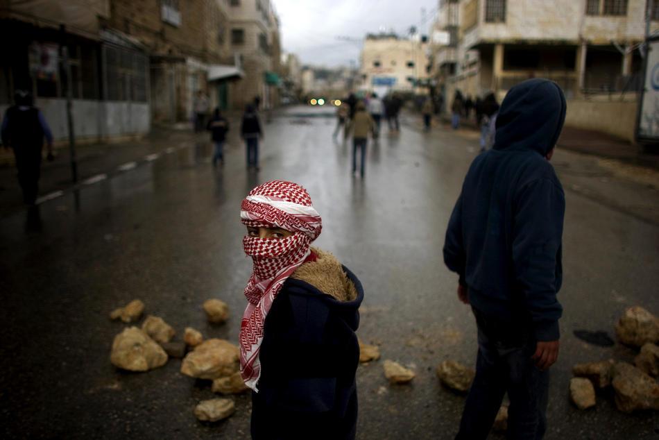 11) Палестинский участник акций протеста в маске во время столкновений в Хевроне, 26 февраля, 2010. Премьер Палестины Салам Файяд молился в Пещере Праотцев, когда шел пятый день столкновений, несмотря на то, что Израиль собирается объявить эту и еще несколько святынь национальным наследием еврейского народа. (AFP PHOTO/DAVID FURST)