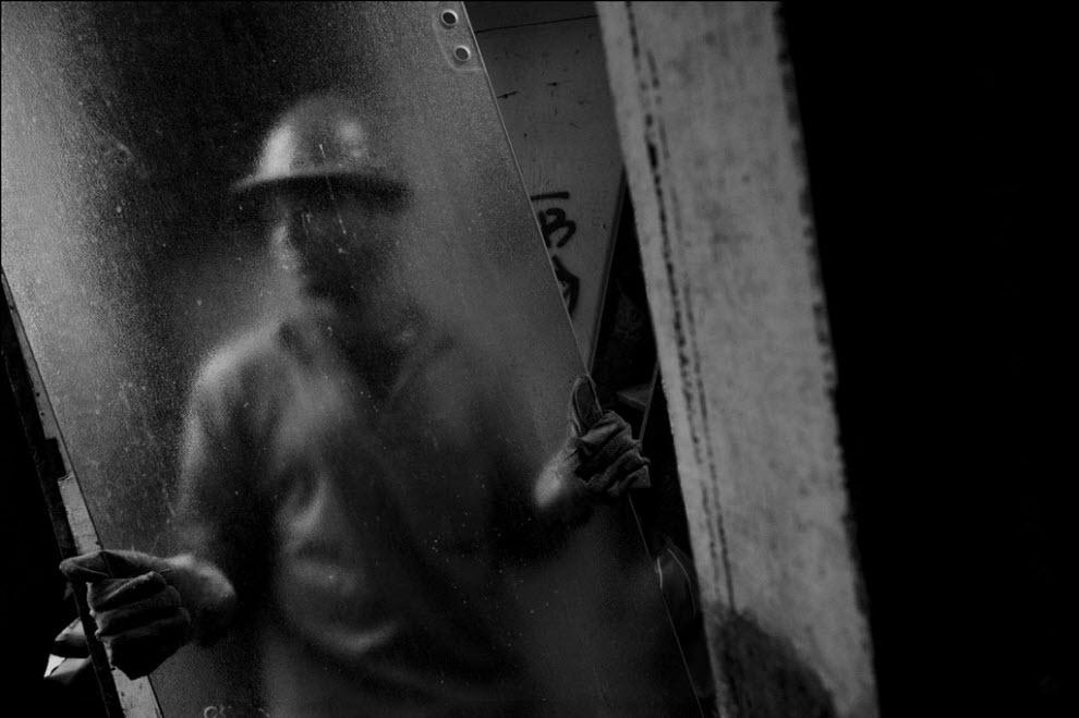 11) Рабочий несет стекло, его коллеги рушат остатки дома.