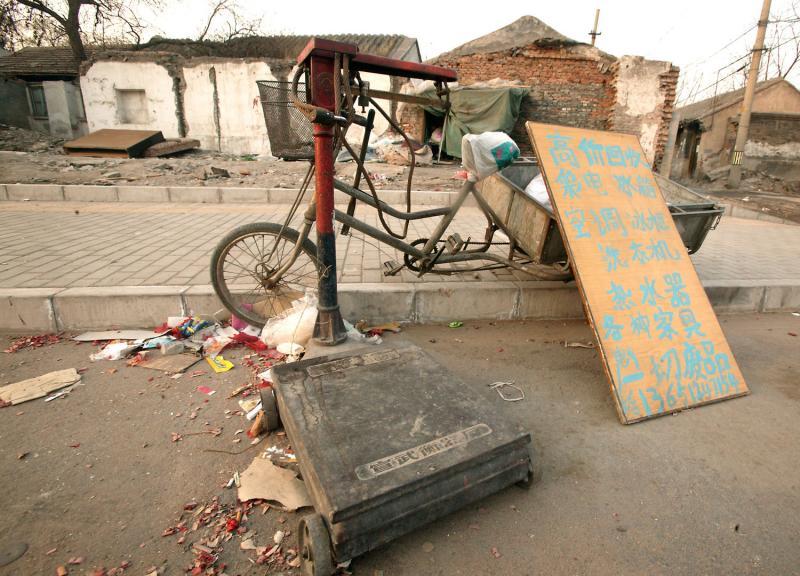 11. Женщина сидит в самодельной лачужке (сзади) у своей точки переработки мусора в старом районе Пекина. В результате отсутствия прав на индивидуальную собственность, вся собственность, находящаяся во владении правительства, и, соответственно, частные лица практически не имеют права слова. Согласно ЮНЕСКО, за последние три года треть старого района площадью 62 кв.км. уже уничтожена. В результате около 580 000 человек остались без домов. (UPI Photo/Stephen Shaver)