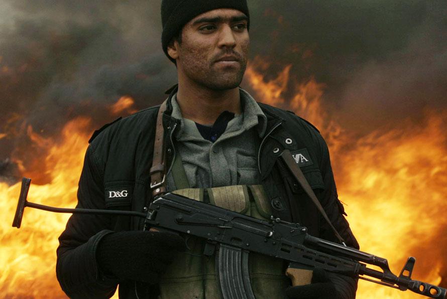 11. Афганский полицейский стоит на фоне огня во время акции по сожжению наркотиков в Герате к западу от Кабула. В Афганистане – крупнейшем производителе опиума в мире – были сожжены более двух тонн наркотиков. (AP Photo/Reza Shirmohammadi)