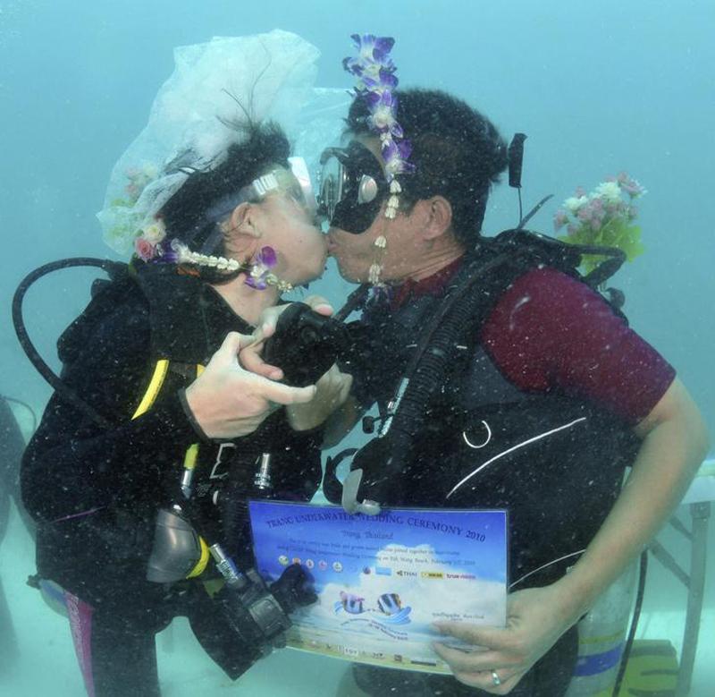 Тайские молодожены целуются во время своей подводной свадьбы, которая прошла 12 февраля 2010 в тайской провинции Транг.