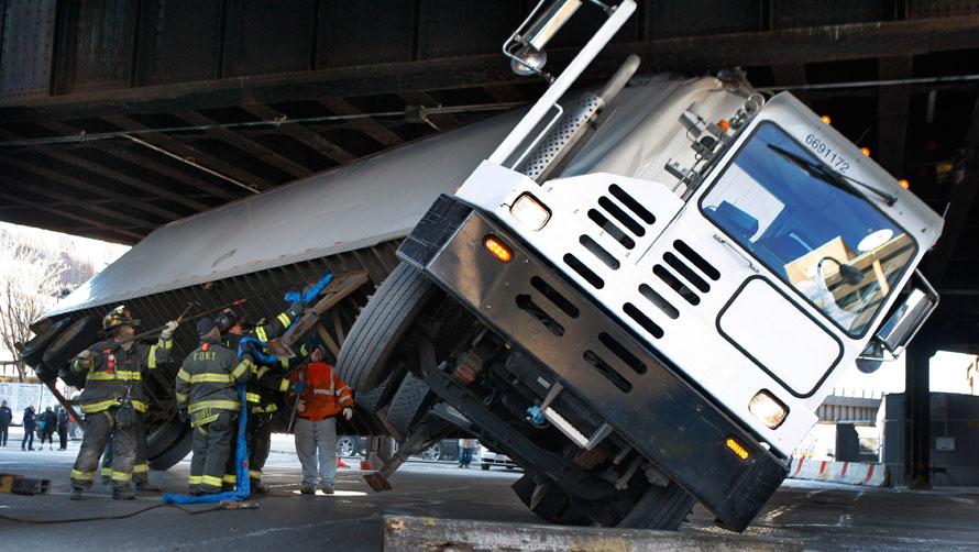 12. Пожарные пытаются освободить грузовик, застрявший под мостом на западной стороне Манхэттена в Нью-Йорке. Грузовик застрял под проездом, поворачивая направо у почтового отделения. Никто не пострадал. (AP Photo/Kathy Willens)