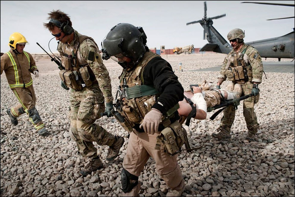12) Раненый американский солдат.US Air Force Pedro Med Evac personnel carry a stretcher with a wounded British soldier from their helicopter into an ambulance in Camp Bastion.