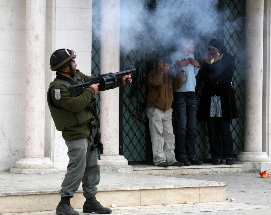 12) Школьники наблюдают за тем, как полиция выстреливает гранаты со слезоточивым газом в толпу протестующей палестинской молодежи, 25 февраля, 2010. Палестинцы проводят акции протеста в Хевроне с тех пор, как 21 февраля 2010 года было объявлено, что Пещера Праотцев и Гробница праматери Рахели, расположенные на территории Палестины, будут включены в список национального наследия еврейского народа. Палестинцы возмущены действиями Израиля. ООН, США и некоторые европейские страны пытаются уладить конфликт. (Rina Castelnuovo/The New York Times)